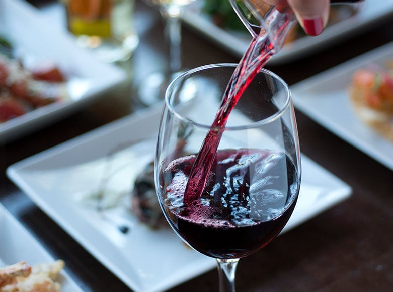 a glass of red wine being poured in front of several plates of tapas